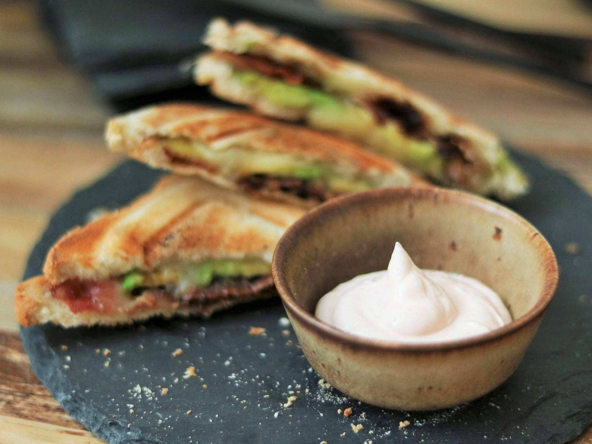 Bacon-Avocado-Sandwich wird in die Aioli getaucht
